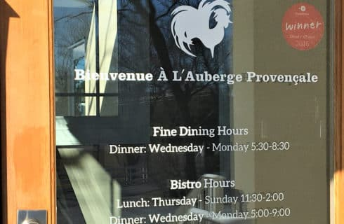Window of restaurant L'Auberge Provencale with rooster logo
