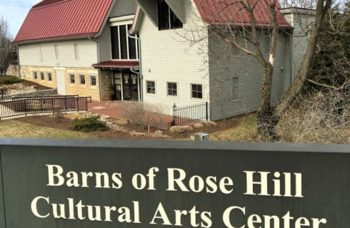 Red roofed white barns with sign Barns of Rose Holl Cultural Arts Center