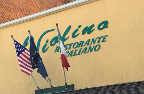 Building with three flags and sign Il Violino Restorante Italiano