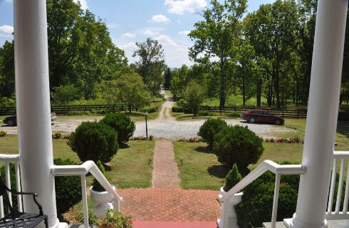 Looking out from porch over a gravel path to a tree-lined trail