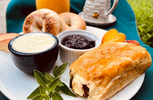 Omelet with tomatoes on top with fruit and sausage