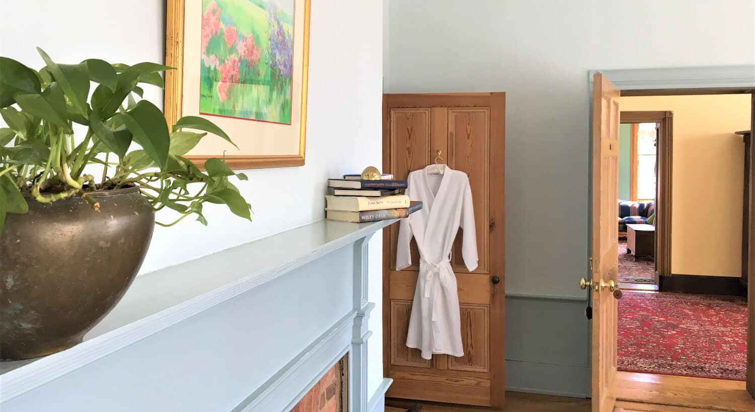 Fireplace mantel of grey panyed wood and door with a fluffy white robe