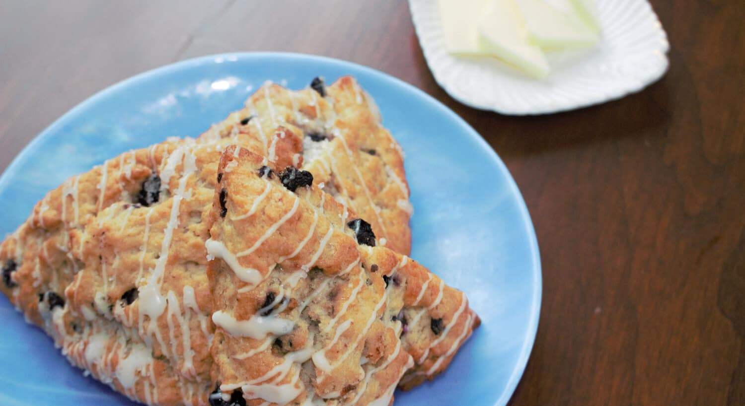 Currant-studded pastries with icing on a blue plate