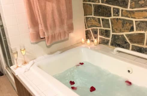 Whirlpoor tub with rose petals flowting in it and candles on ledge