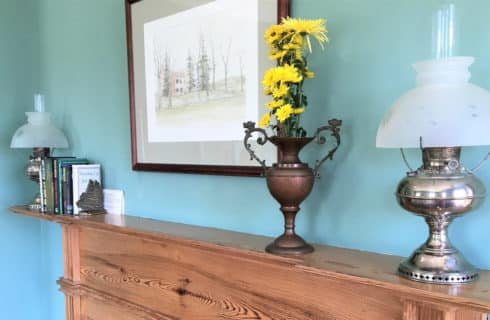 Wooden fireplace mantel with a brass lamp and vase of yellow flowers