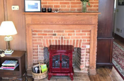 Brick fireplace with wooden mantel and red fireguard
