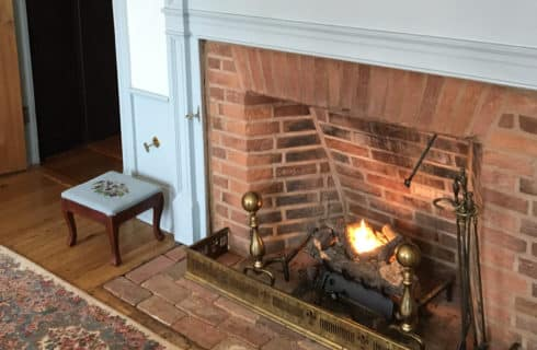 Large brick fireplace with fire burning merrily