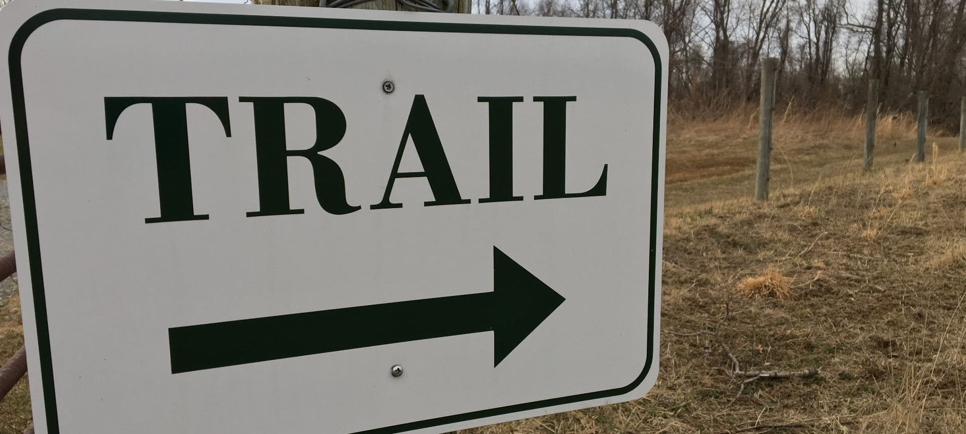 Metal sign on a post with the word Trail and a black arrow