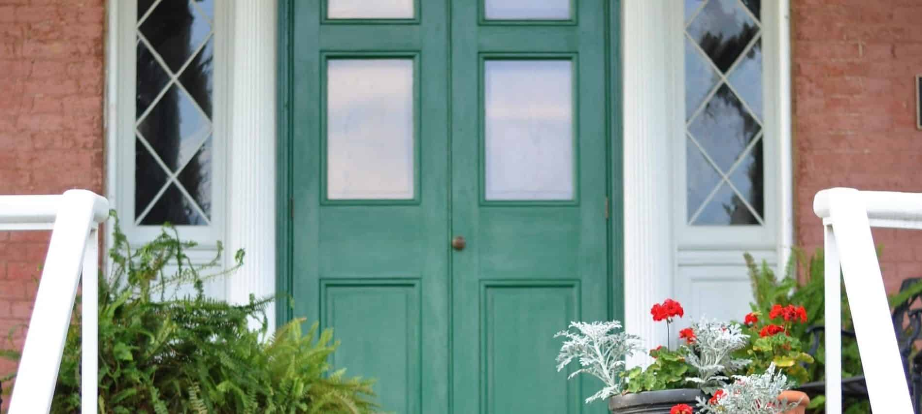Red brick front porch with green door and white trim and potted plants on stairs