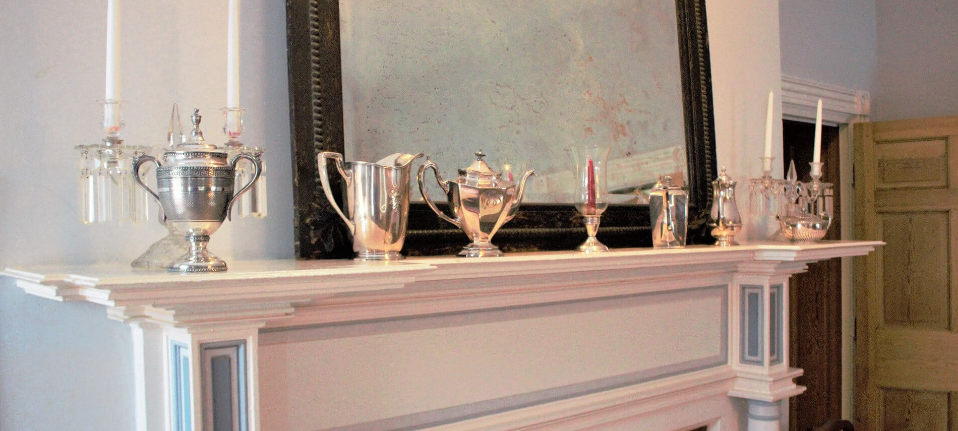 White fireplace mantel with silver cups on top