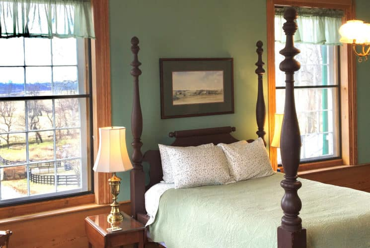 Large wooden four poster bed with pale green bedding in a light filled guest room