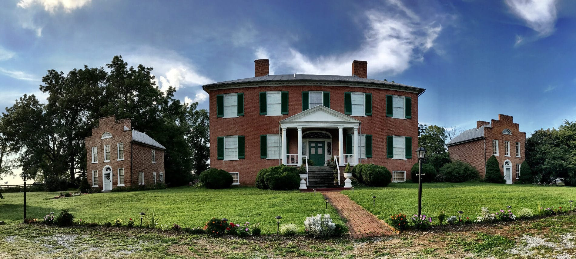 Large brick manor house with white columns and two firestacks