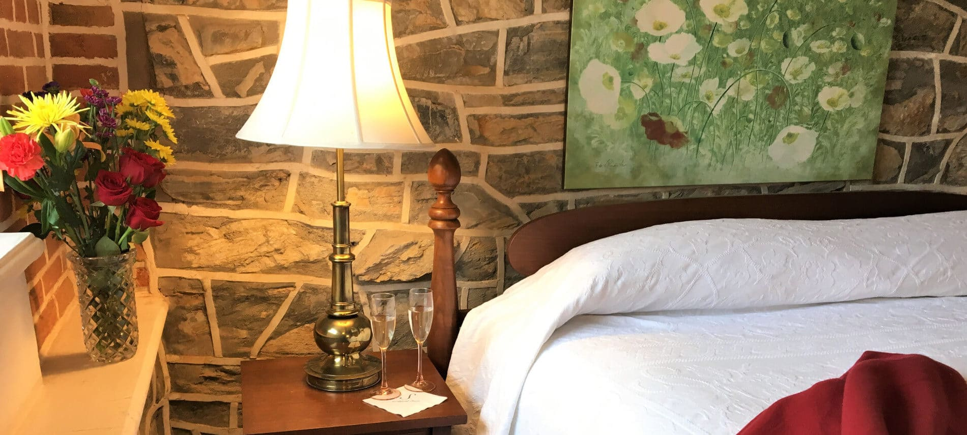 Cozy bed set against a stone wall with a cheerful lamo on a wooden bedside table