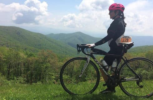 Woman in biking clothes on bike looks over green mountains