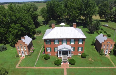 Large brick manor house with green shutters and expansive lawns