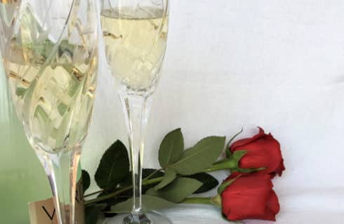 Two flutes of champagne with red roses
